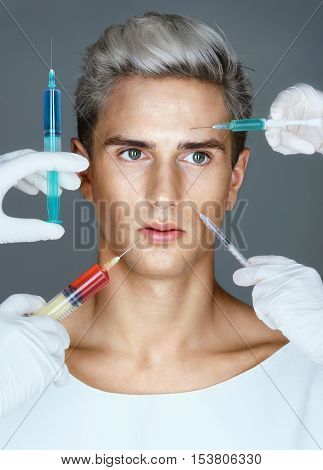 Beauty through botox. Photo of young man with four injection needle pointed at his face. Injections of skin rejuvenation. Cosmetic procedures