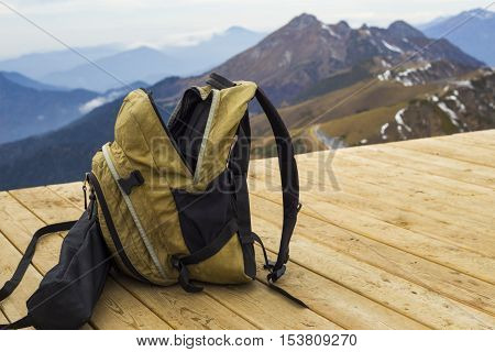 Yellow hipster rucksack on wooden floor at mountains background