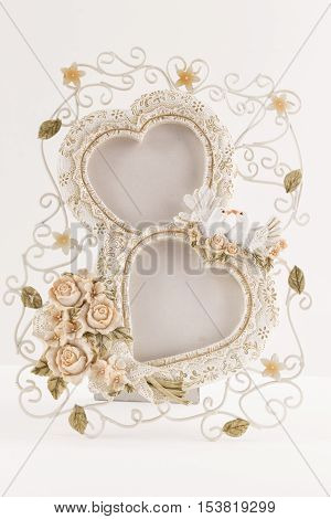 vertical image of a picture frame of two hearts mid an intertwined wire of flowers and lace imitation and two white doves on white background with room for text great for greeting