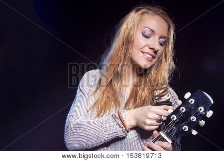 Musical Concepts and Ideas. Caucasian Blond Female Posing with Guitar Against Black. Horizontal Image Orientation