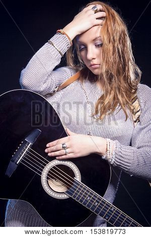 Musical Concepts and Ideas. Portrait of Caucasian Blond Female Posing with Guitar Against Black. Vertical Image