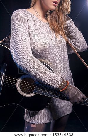 Music Styles Concepts and Ideas. Young Caucasian Female Music Player Posing with Guitar Against Black. Combination of Flash and Halogen Used. Vertical Image