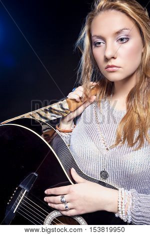Musical Concepts and Ideas. Portrait of Sad Looking Caucasian Blond Female Posing with Guitar Against Black. Vertical Composition
