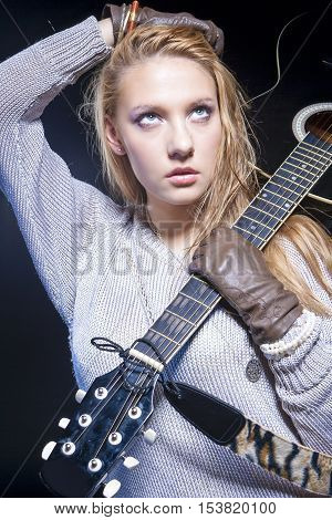 Portrait of Blond Caucasian Woman Posing With Acoustic Guitar Against Black Background. Vertical Image Orientation