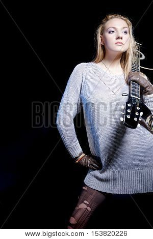 Musical Concepts and Ideas. Caucasian Blond Female Posing with Guitar Against Black. Vertical Shot