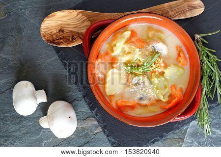 Creamy Tortellini And Mushroom Soup In An Orange Soup Bowl, Overhead Scene On Slate