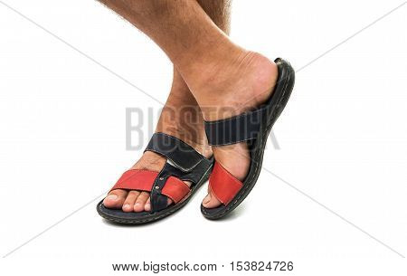 Men's feet in leather sandals on a white background