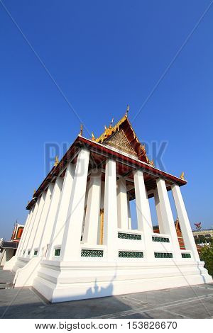 White pillars of the ordination hall at Wat Ratchanadda temple on blue sky background Bangkok Thailand