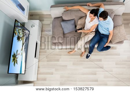 High Angle View Of Young Couple Watching Movie On Television At Home