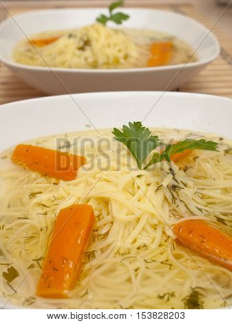 broth with noodles, carrot on a white plate
