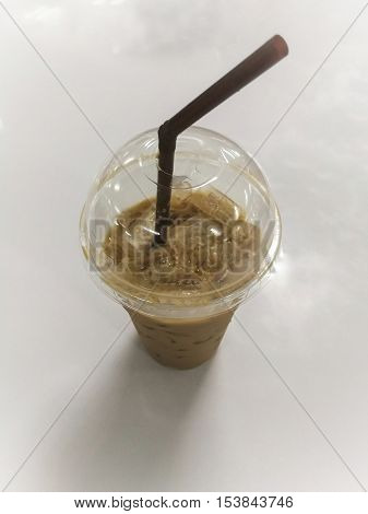 Ice coffee in the plastic glass on the table.