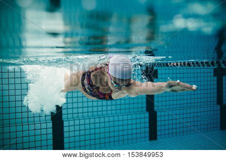 Underwater shot of female athlete swimming in pool. Young woman swimming the front crawl in a pool.
