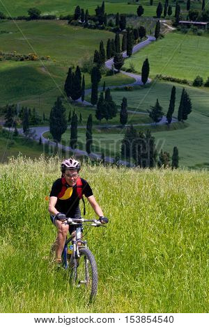 Val d'Orcia Siena mountain bike excursion in the Tuscan hills - winding avenue of Monticchiello seen from Podere La Piana