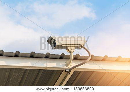 The Close Circuit Camera On The Roof With The Blue Sky Background. The Security System From The Clos