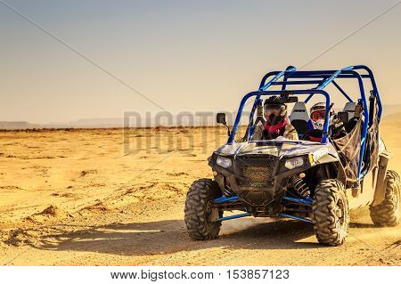Merzouga Morocco - Feb 24 2016: front view on blue Polaris RZR 800 with it's pilots in Morocco desert near Merzouga. Merzouga is famous for its dunes the highest in Morocco.
