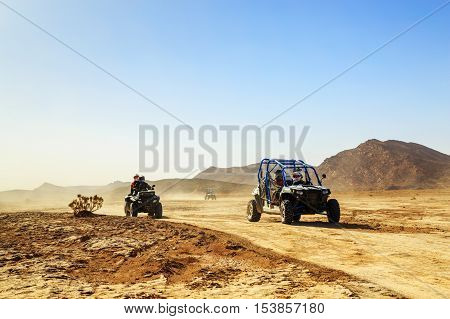 Merzouga Morocco - Feb 24 2016: convoy of off-road vehicles (RZR Quad and motorbikes) in Morocco desert near Merzouga. Merzouga is famous for its dunes the highest in Morocco.