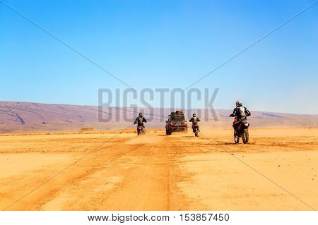 Merzouga Morocco - Feb 22 2016: convoy of off-road vehicles (4x4 and motorbikes) in Morocco desert near Merzouga. Merzouga is famous for its dunes the highest in Morocco.