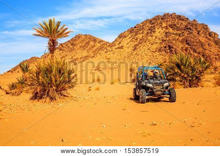 Merzouga Morocco - Feb 26 2016: front view on blue Polaris RZR 800 with it's pilots in Morocco desert near Merzouga. Merzouga is famous for its dunes the highest in Morocco. There is a palm grove in the background