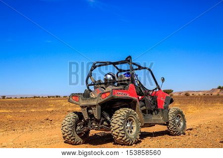 Merzouga Morocco - Feb 23 2016: back view on red Polaris RZR 800 with it's pilots in Morocco desert near Merzouga. Merzouga is famous for its dunes the highest in Morocco.