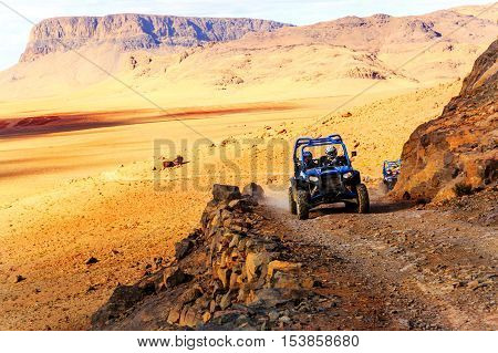 Merzouga Morocco - Feb 21 2016: blue Polaris RZR 800 crossing a mountain road in the Moroccan desert near Merzouga. Merzouga is famous for its dunes the highest in Morocco.