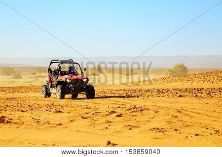 Merzouga Morocco - Feb 22 2016: front view on blue Polaris RZR 800 with it's pilots in Morocco desert near Merzouga. Merzouga is famous for its dunes the highest in Morocco.