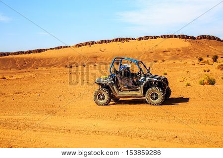 Merzouga Morocco - Feb 26 2016: Side view on blue Polaris RZR 800 with it's pilots in Morocco desert near Merzouga. Merzouga is famous for its dunes the highest in Morocco.
