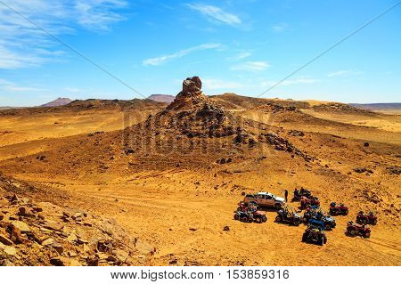 Merzouga Morocco - Feb 26 2016: top view on group of off-road pilots during a break in Morocco desert near Merzouga. Merzouga is famous for its dunes the highest in Morocco.