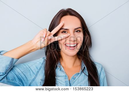 Pretty Cheerful Woman Gesturing With Two Fingers Near Eyes