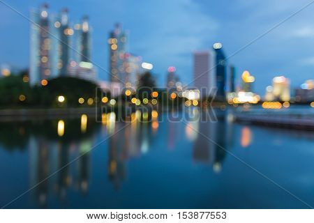 Twilight blurred bokeh lights reflection of city office building in public park, abstract background