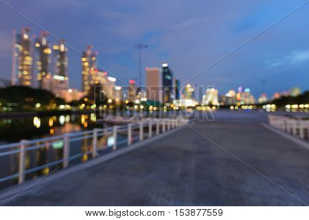 Abstract blurred bokeh lights walking way in public park with city office building background