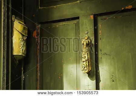 Close up of a door with flaked green paint, red under coat. Gold door knocker and gold paper holder. Savannah USA