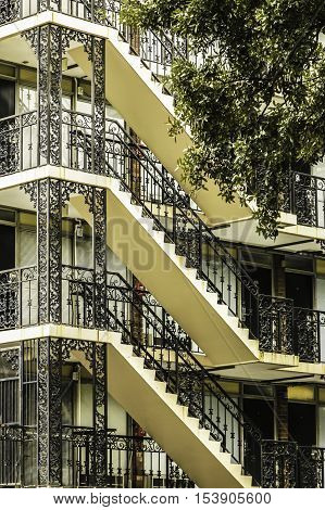 External stairs with decorative black iron lace railings on a three story building in Savannah USA.