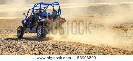 Merzouga Morocco - Feb 25 2016: Panoramic view on Blue Polaris RZR 800 with it's pilot in Morocco desert near Merzouga. Merzouga is famous for its dunes the highest in Morocco.