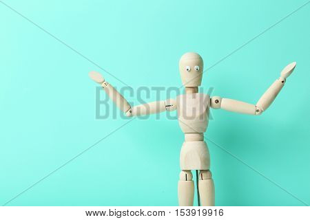 Wooden Figure With Googly Eyes On A Green Background