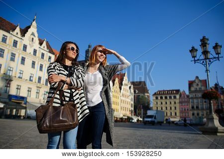 Two attractive girlfriends stand in cobbled square of beautiful city. One of women in dark glasses other covered her eyes with her hand. Behind them are beautiful old buildings. Bright blue sky.