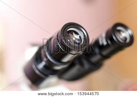Laboratory microscope. Close-up view of ocular lenses in binocular microscope