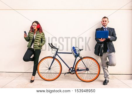 Woman and business man using mobile phone and pc leaning on white wall - Urban concept of connected people and modern tecnology addiction