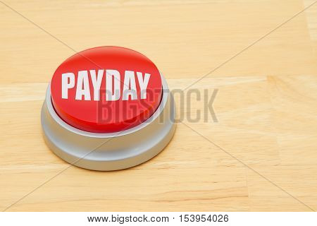 A Payday red push button A red and silver push button on a wooden desk with text Payday