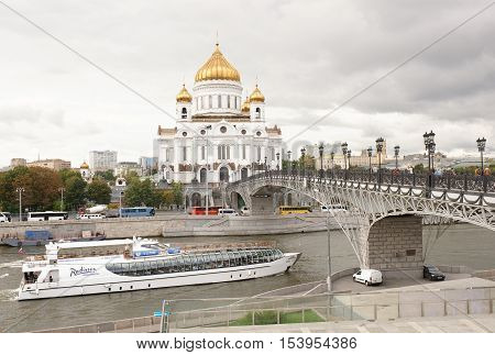 Moscow Russia -September 09 2016: Cathedral of Christ the Savior and the Patriarchal bridge. Through the bridge moving pedestrians. On the river float vessels