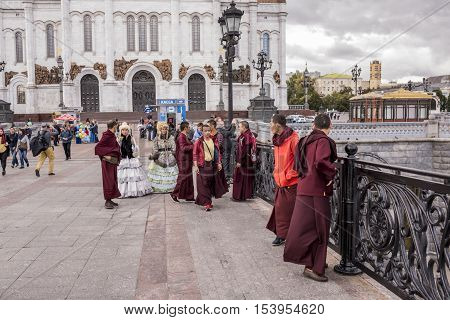 Moscow Russia -September 092016: Roma women in ancient dresses make a fool of Tibetan monks at the Patriarchal bridge