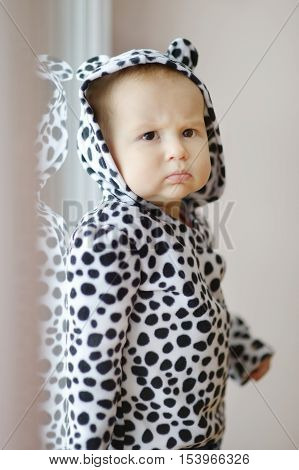 Adorable little girl in spotty hoody by the window