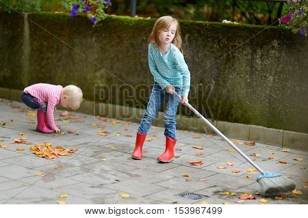 Cute Little Girls Sweeping Dry Leaves On Autumn