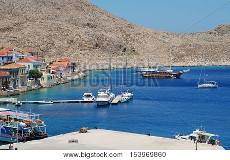 HALKI, GREECE - JULY 15, 2015: Boats moored in the harbour at Emborio on the Greek island of Halki. The harbour forms the hub of the islands main industries of fishing and tourism.