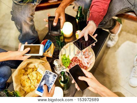 Top view of multiracial young friends using phone and toasting aperitif - Closeup of hands social networking with mobile cellphones - Technology addiction concept - Soft focus on right top hand