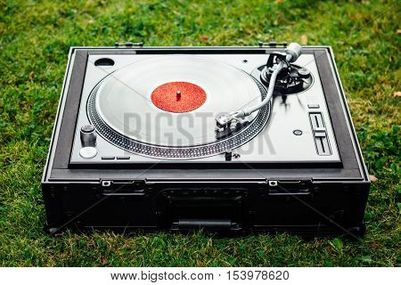 turntable with LP vinyl record on green grass background