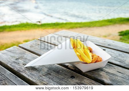 Traditional australian calamari rings with chips take away on the table at Port Elliot beach South Australia