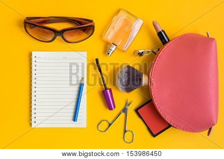 Top view of open notepad and blue pencil surrounded by cosmetic products - make up brush brush on scissors mascara eyelash curler lipstick perfume glasses and bag on yellow background