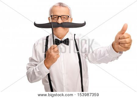Elderly gentleman in a bow tie and suspenders posing with a big fake moustache and giving a thumb up isolated on white background