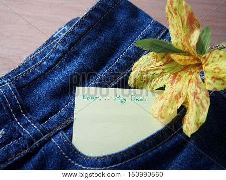 Dear my dad short note on sticky paper in jean pants bag, decorated with handmade flower