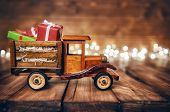 Merry Christmas and Happy Holidays! Gifts boxes presents on toy car and Christmas garland lights on  poster
